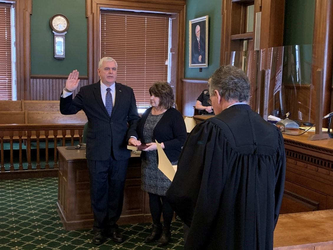 Assemblyman Joseph Angelino (R,C,I-Norwich) is sworn into his assembly office by NYS Supreme Court Justice Joseph McBride while the assemblyman's wife, Kendall Saber, holds the family bible.